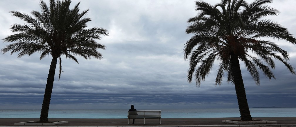 Palm trees frame a man who sits on a bench on a winter's day along the Promenade Des Anglais in Nice February 4, 2015.