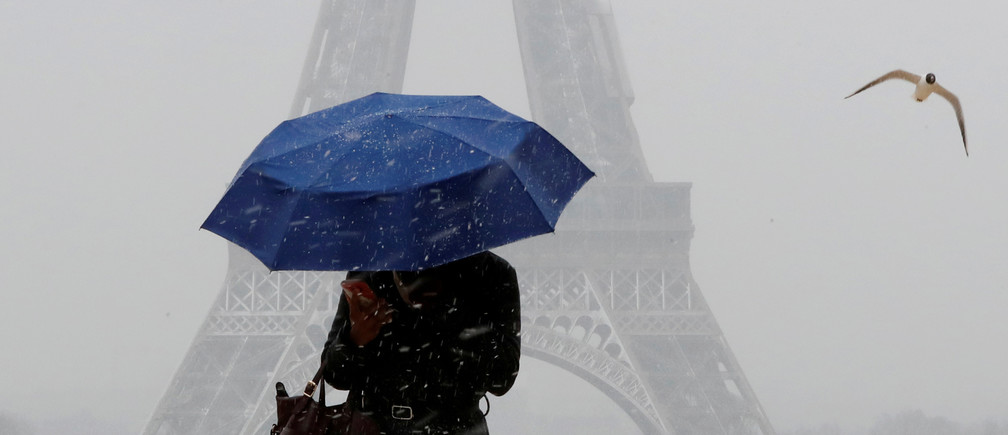A woman holds an umbrella to protect herself from falling snow near the Eiffel Tower in Paris, as winter weather with snow and freezing temperatures arrive in France, February 6, 2018. REUTERS/Gonzalo Fuentes     TPX IMAGES OF THE DAY - RC12BBCF1B40