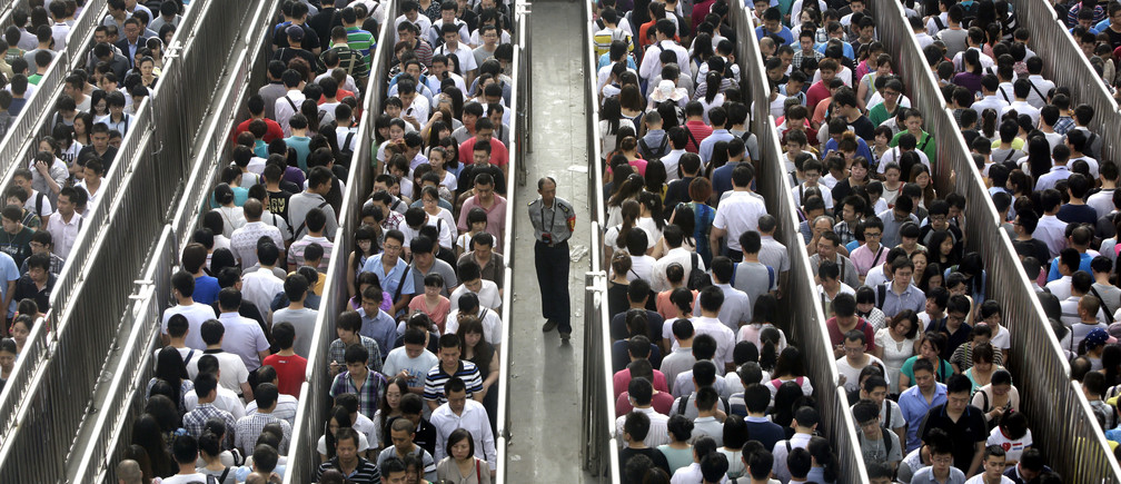 A security officer stands guard as passengers line up and wait for a security check during morning rush hour at Tiantongyuan North Station in Beijing May 27, 2014. Beijing tightened security checks at subway stations since last Saturday, following an attack in China's troubled Xinjiang region which killed 31 people on May 22, the deadliest act of violence in the region in years. REUTERS/Jason Lee (CHINA - Tags: CIVIL UNREST CRIME LAW TPX IMAGES OF THE DAY TRANSPORT) - GM1EA5R0S1D01