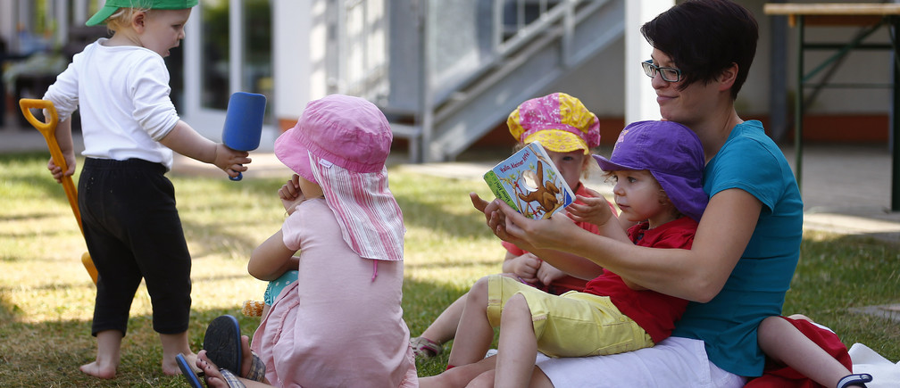 Children listen to a story read by their nursery school teacher while sitting in the outdoor area of the Kathinka-Platzhoff-Stiftung Kindergarten (Kathinka-Platzhoff-foundation kindergarden) in Hanau, 30km (18 miles) south of Frankfurt, July 16, 2013. From August 1, 2013, all children in Germany between the age of 1 and 3 will have a legal entitlement to a place at a kindergarten. The Kindergarten of the Kathinka-Platzhoff-Stiftung is one of few which hosts children between the age of six month and six years.  Picture taken July 16. REUTERS/Kai Pfaffenbach (GERMANY - Tags: POLITICS BUSINESS EMPLOYMENT SOCIETY EDUCATION) - BM2E97G14L401