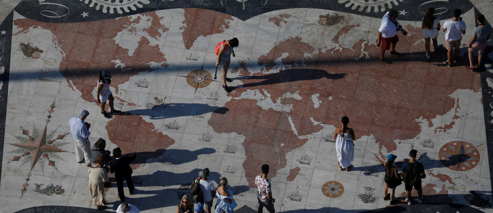 People take pictures at a square decorated with a giant world map in Lisbon, Portugal September 6, 2017. REUTERS/Rafael Marchante - RC15DA1863E0