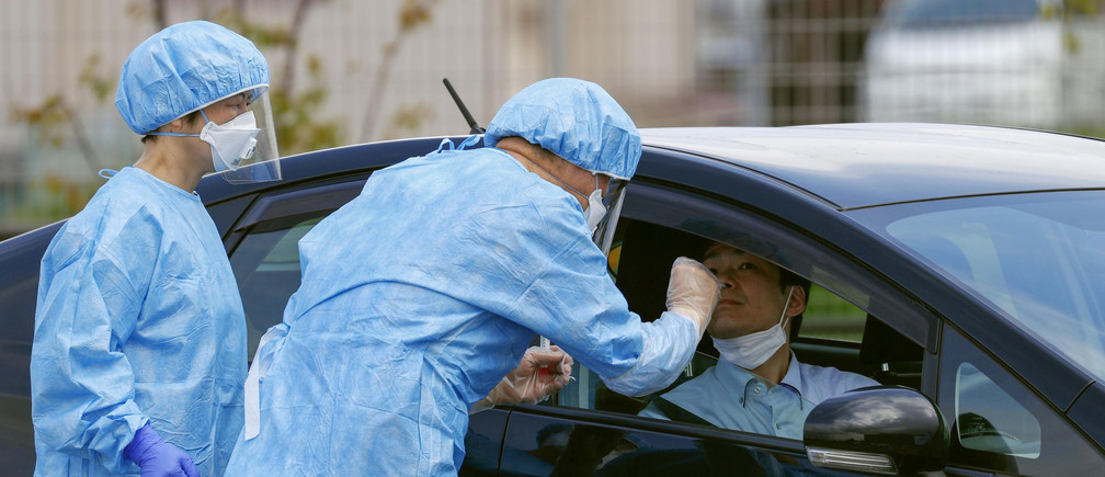 Medical workers carry out a mock drive-through testing for the coronavirus disease (COVID-19) in Nara, Japan in this photo taken by Kyodo April 20, 2020. Mandatory credit Kyodo/via REUTERS ATTENTION EDITORS - THIS IMAGE WAS PROVIDED BY A THIRD PARTY. MANDATORY CREDIT. JAPAN OUT. - RC2B8G98HT98