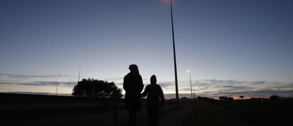 "An Eritrean mother and her daughter are seen in silhouette as they walk along the motorway near the Channel Tunnel entrance near Calais, France, August 6, 2015. For most of the 3,000 inhabitants of the ""Jungle"", a shanty town on the sand dunes of France's north coast, the climax of each day is the nightly bid to sneak into the undersea tunnel they hope will lead to new life in Britain. REUTERS/Peter Nicholls"