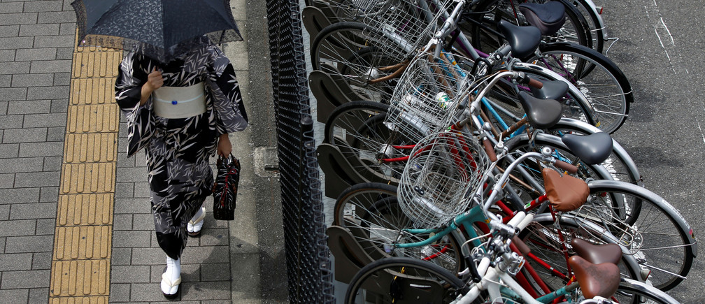 A kimono-clad woman holding a parasol walks next to a cycle parking lot near a railway station in Tokyo, Japan August 29, 2017. REUTERS/Issei Kato
