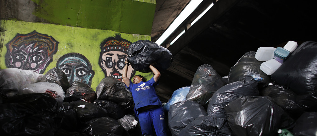 "Garbage recycler Marilene Barbosa, 44, throws a bag of trash onto a pile under the Glicerio viaduct in downtown Sao Paulo March 14, 2014. Brazil generates 250,000 tons of waste every day, according to official estimates, and the city of Sao Paulo is the biggest contributor to that with 19,000 tons. Under the Glicerio viaduct, workers known as ""catadores"" select material to send to recycling centers, amounting up to some 100 tons each month. Picture taken March 14, 2014. REUTERS/Nacho Doce (BRAZIL - Tags: ENVIRONMENT SOCIETY) - GM1EA4N0A4F01"