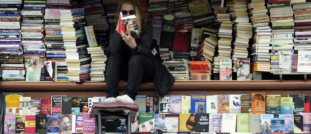 A woman reads a book at her open air book store.