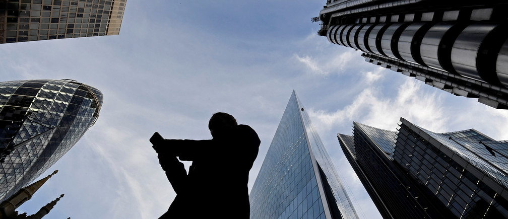 A worker looks at their phone as they walk past The Gherkin, Lloyds, and other office buildings in the City of London, Britain November 13, 2018. REUTERS/Toby Melville - RC1A2B2C9040