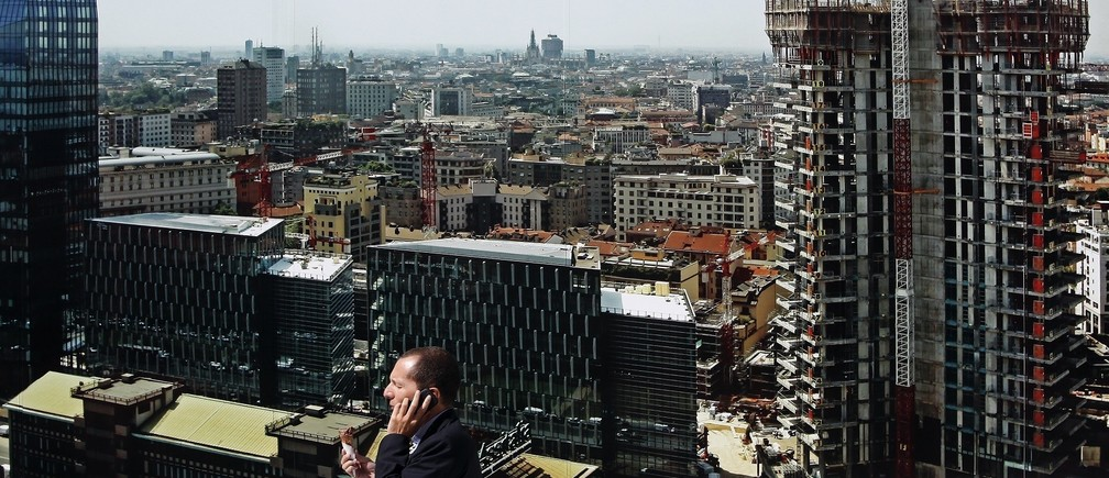 A man talks on his phone in downtown Milan September 12, 2013. Italian bond yields rose on Thursday and the country paid more to raise funds at an auction, highlighting investor concerns about a political crisis that some worry could stall efforts to revive the economy. Rome sold the maximum planned amount of 7.5 billion euros and demand for its three-year bond was higher than at an auction of similar paper in July.     REUTERS/ Stefano Rellandini ( ITALY - Tags: POLITICS BUSINESS) - RTX13IRU