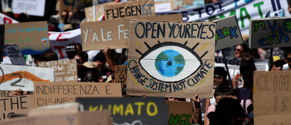 People hold up signs as they take part in a climate strike after the five-day Summer Meeting in Lausanne Europe (SMILE) of the Fridays for Future movement in Lausanne, Switzerland August 9, 2019. REUTERS/Denis Balibouse - RC1C431AA8F0