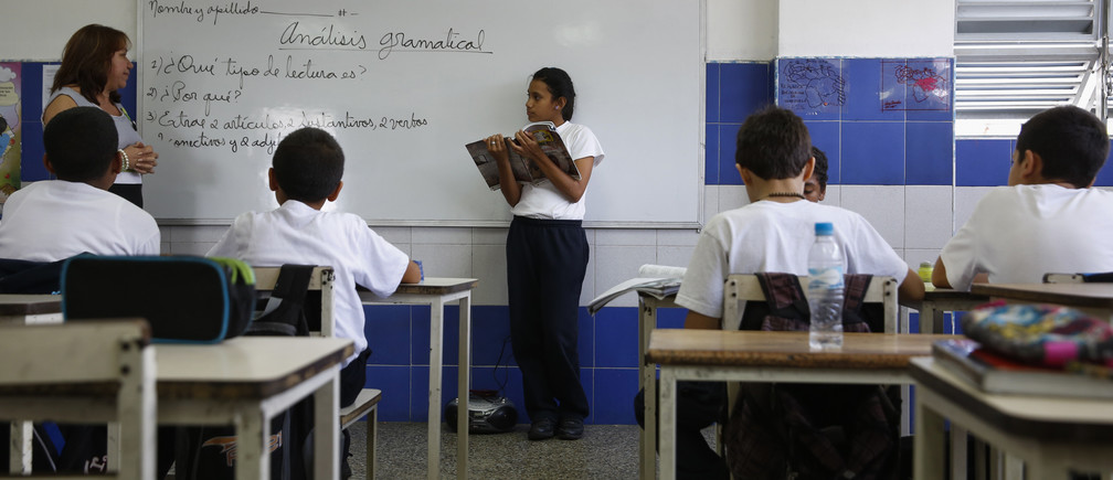 "A girl reads a state-issued textbook from the ""Bicentennial Collection"" in front of her classmates at a classroom of the Eleazar Lopez Contreras school in Caracas May 23, 2014. Venezuela's government has published dozens of new textbooks that glorify late president Hugo Chavez and belittle his adversaries, infuriating opposition critics who call them part of a campaign to indoctrinate school children. Originally introduced in mid-2011, the textbooks have become a hot-button issue again amid a broad state-run review of the education system that some fear could boost the ruling Socialist Party's imprint on classrooms. Picture taken on May 23, 2014. REUTERS/Carlos Garcia Rawlins (VENEZUELA - Tags: EDUCATION POLITICS) - GM1EA6300QX01"