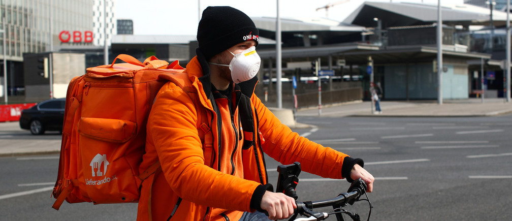 A food delivery worker wears a protective mask, during the coronavirus disease (COVID-10) outbreak, in Vienna, Austria March 26, 2020