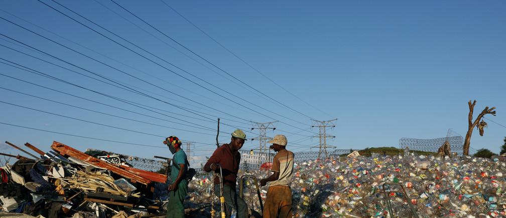 Men sort waste materials including plastic bottles in Soweto, South Africa.