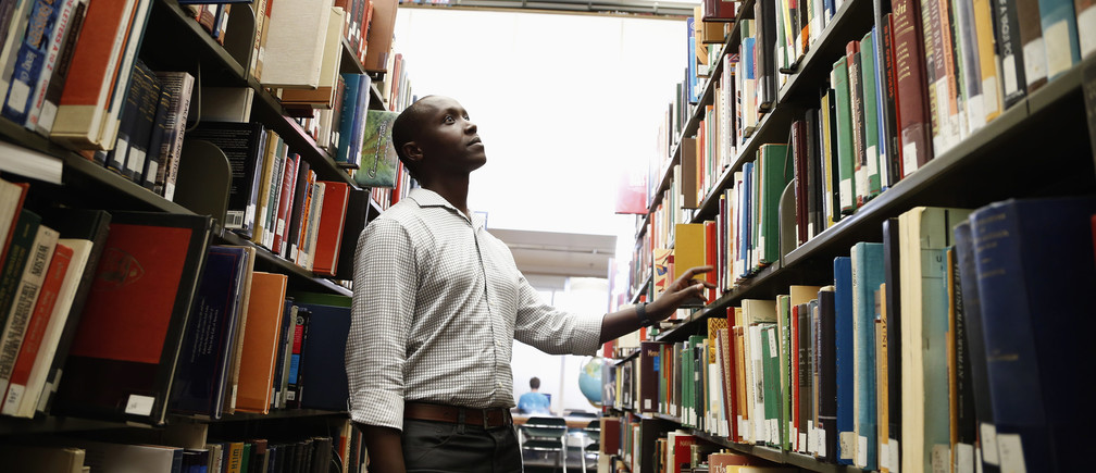 Patrick Manyika, 33, of Rwanda looks for a book in the library at the University of Redlands where he will starting his second master's degree in Geographic Information Systems, in Redlands, California May 28, 2014. Manyika was born in a Ugandan refugee camp after his Tutsi family fled Rwanda. In 1983, unrest forced them back to Rwanda, where they lived first in a national park, then in the capital. Manyika survived the Rwandan genocide of 1994, in which 800,000 Tutsis and moderate Hutus were killed, by sheltering in a UN-controlled soccer stadium. After doing charity work and teaching himself various languages, in 2009 he had the opportunity to leave Rwanda and pursue his education in the United States. He is now about to start his second Masters degree. June 20 is World Refugee Day, an occasion that draws attention to those who have been displaced around the globe. In the run-up to the date, Reuters photographers in different regions have photographed various people who have at some point fled their homes. Picture taken May 28, 2014. REUTERS/Lucy Nicholson  (UNITED STATES - Tags: SOCIETY IMMIGRATION POLITICS EDUCATION) ATTENTION EDITORS: PICTURE 18 OF 36 FOR PACKAGE 'WORLD REFUGEE DAY - A LIFE DISPLACED'TO FIND ALL IMAGES SEARCH 'REUTERS GLOBAL REFUGEE' - GM1EA6I1CWB01