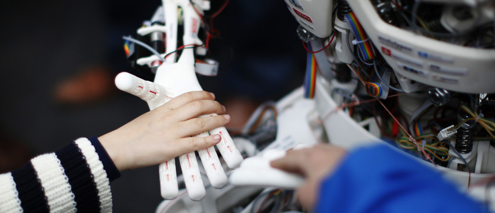 Children touch the hands of the humanoid robot Roboy at the exhibition Robots on Tour in Zurich, March 9, 2013. A project team composed of scholars and industry representatives developed the prototype of the tendon driven humanoid robot Roboy within nine months.  Roboy was unveiled to the public today during the exhibition that is marking the 25th anniversary of the Artificial Intelligence Laboratory of the University of Zurich (AI Lab). REUTERS/Michael Buholzer (SWITZERLAND - Tags: SCIENCE TECHNOLOGY SOCIETY BUSINESS) - BM2E93916AH01