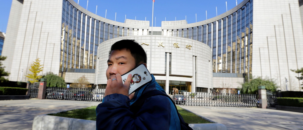 A man uses his mobile phone while walking past the headquarters of the People's Bank of China (PBOC), the central bank, in Beijing, November 20, 2013.      REUTERS/Jason Lee/File Photo - RTX2PSUT