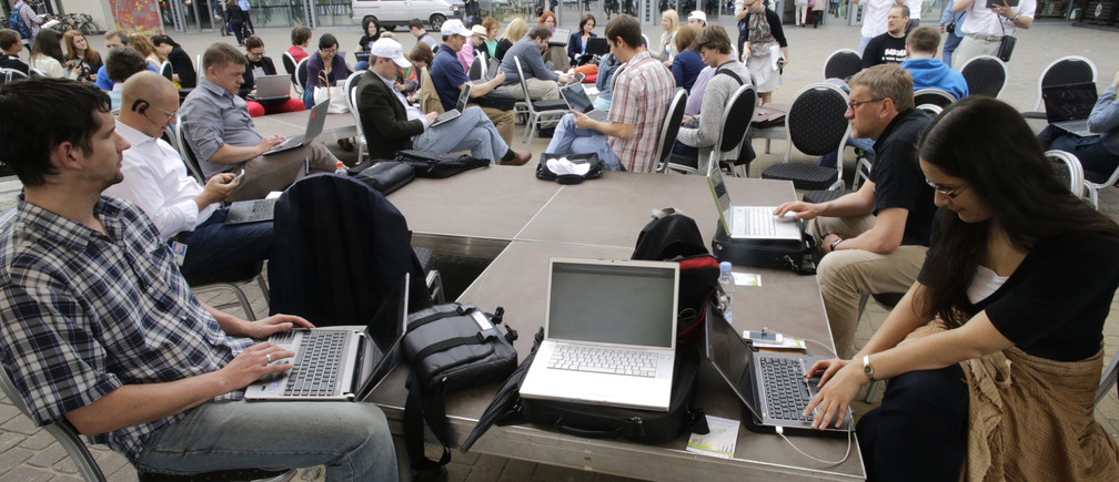 "People use their laptops during ""Working everywhere"" event in Riga May 31, 2013. More than 150 activists with laptops and wi-fi access attended event to demonstrate the benefits of flexible working style and possibly set a new Guinness world record for ""Most people who work in a specific place outside the office"". REUTERS/Ints Kalnins (LATVIA - Tags: SOCIETY) - GM1E961053P01"