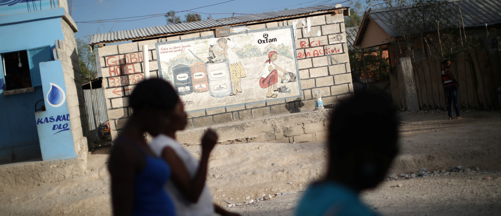 Women walk past an Oxfam sign in Corail, a camp for displaced people of the 2010 earthquake, on the outskirts of Port-au-Prince, Haiti, February 13, 2018. REUTERS/Andres Martinez Casares - RC16E88E40B0