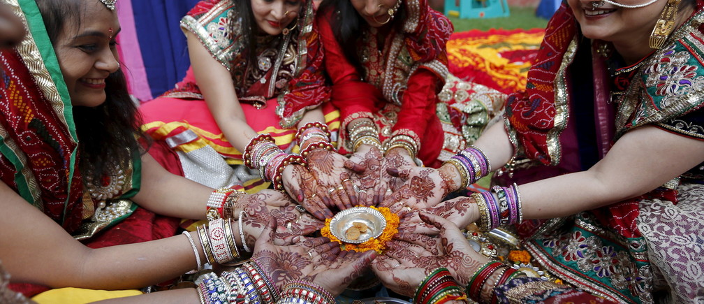 Women with their hands decorated with henna paste pose for pictures as they pray during the Hindu festival of Karva Chauth in Ahmedabad, India, October 30, 2015. Married Hindu women observe a one-day fast and offer prayers for the well-being of their husbands during the festival. The fast begins before sunrise and ends after they worship the moon in the evening. REUTERS/Amit Dave - RTX1TYZU