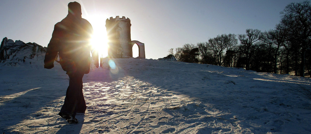 A walker strides through snow towards the Old John memorial in Bradgate Park, Leicestershire in northern England, January 29, 2004. Commuters faced severe delays across Britain on Thursday after freezing weather brought chaos to roads, railways and airports. NO RIGHTS CLEARANCES OR PERMISSIONS ARE REQUIRED FOR THIS IMAGE REUTERS/Darren Staples   DS/ASA/JB - RP4DRIGUPAAB