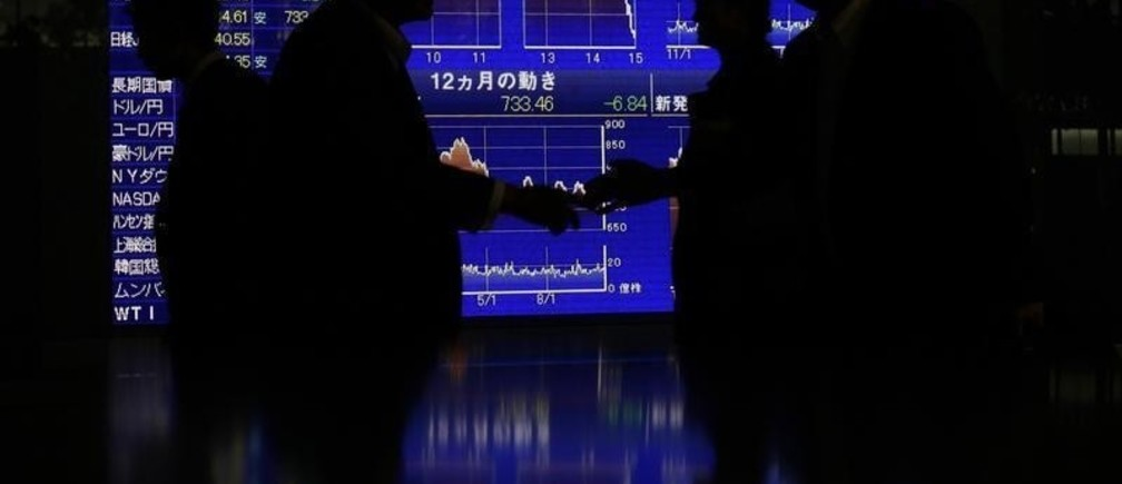 People shake hands in front of an electronic board displaying a graph of Japan's Nikkei share average and other market indices outside a brokerage in Tokyo October 30, 2012. Japan's Nikkei average fell 1 percent to a two-week closing low on Tuesday after the Bank of Japan eased monetary policy by increasing the size of its asset buying and lending programme by $138 billion, largely as expected. REUTERS/Yuriko Nakao (JAPAN - Tags: BUSINESS) - GM1E8AU1FVT01