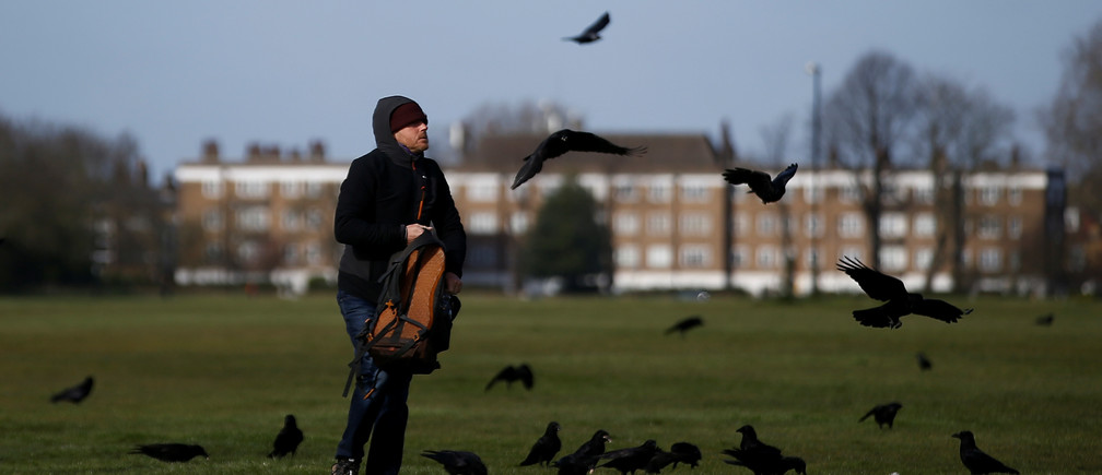 A man feeds some birds on Blackheath Common, as the spread of the coronavirus disease (COVID-19) continues, London, Britain, March 29, 2020. REUTERS/Henry Nicholls - RC2LTF9EDD5D