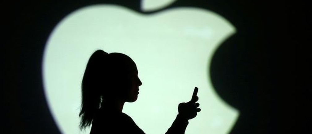 Silhouette of mobile user is seen next to a screen projection of Apple logo in this picture illustration taken March 28, 2018.  REUTERS/Dado Ruvic/Illustration