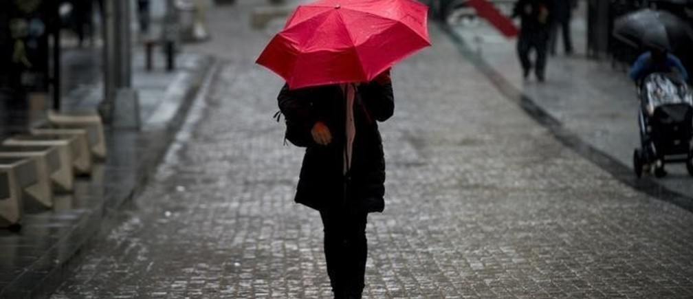 A woman walks on Broad St. past the New York Stock Exchange during the morning commute April 30, 2014. REUTERS/Brendan McDermid (UNITED STATES - Tags: BUSINESS TPX IMAGES OF THE DAY)