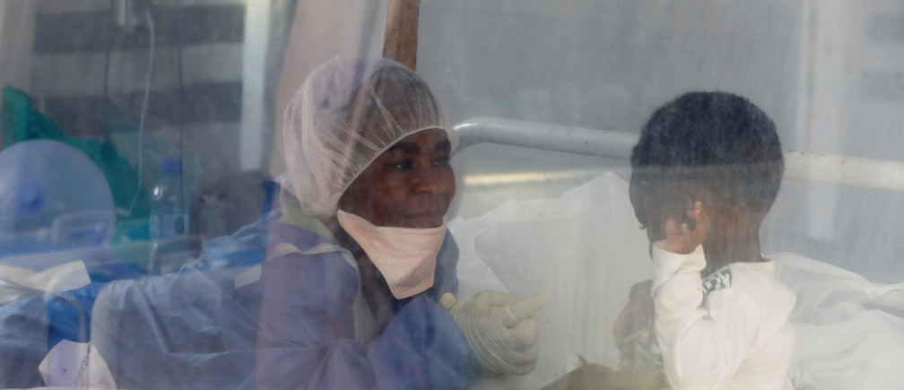 """Noella Masika Vinyinyi, 30, an Ebola survivor who works as a caregiver, takes care of Angeline Kalala, 1, who is suspected to be suffering from Ebola, inside the Biosecure Emergency Care Unit (CUBE) at an Ebola treatment centre (ETC) in Katwa, near Butembo, in the Democratic Republic of Congo, October 3, 2019. Masika survived  Ebola in June 2019. She lost 17 family members to Ebola, including both parents and two grandparents, but she counts herself fortunate to have survived. """"I feel compassionate and grateful for the care I received,"""" she said. """"I feel an obligation to contribute to the fight against Ebola."""" REUTERS/Zohra Bensemra   SEARCH """"EBOLA ZOHRA"""" FOR THIS STORY. SEARCH """"WIDER IMAGE"""" FOR ALL STORIES. - RC135078D6A0"""