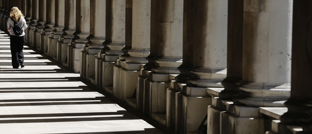 A woman walks through shadows cast by columns at the Old Royal Naval College in Greenwich east London June 10, 2014.   REUTERS/Luke MacGregor