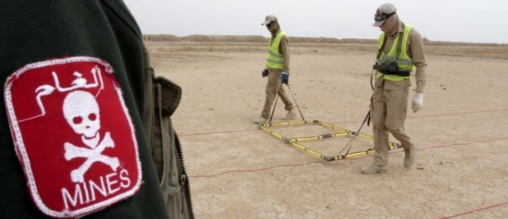 De-mining teams searches for landmines in the desert east of Basra province, April 1, 2015. In Iraq's vast southern desert, de-mining teams are working to remove millions of Saddam-era landmines and explosive ordnance that litter Iraq's southern giant oil fields, hampering the country's oil boom and delaying investment. Picture taken April 1 2015.  REUTERS/Essam Al-Sudani  - GF10000051566