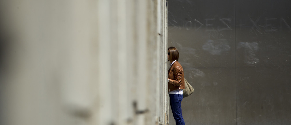 A woman looks through a crack in a concrete barrier that is part of the former Berlin Wall border fortification at the memorial site in Bernauer Strasse in Berlin, August 13, 2012.