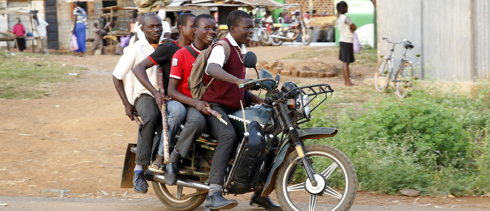 Secondary school students ride on a motorbike past the trading centre in the U.S. President Barack Obama's ancestral village of Nyang'oma Kogelo, west of Kenya's capital Nairobi, July 15, 2015.