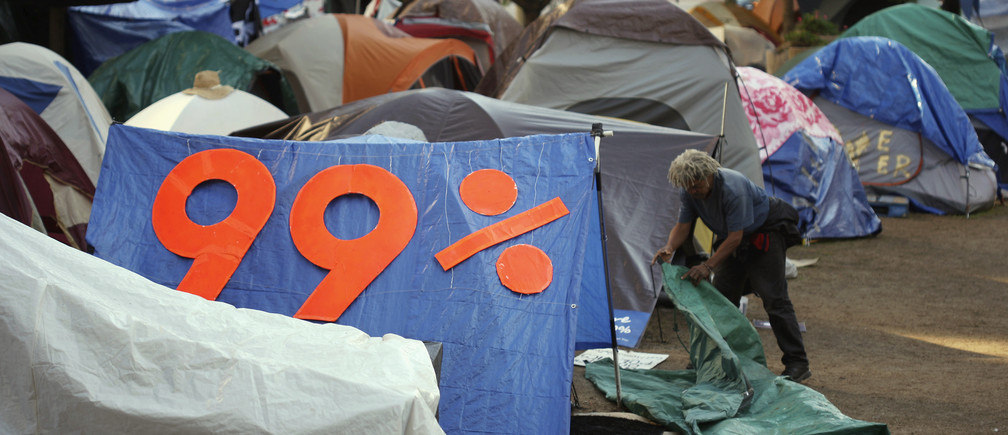 A man packs his personal belongings next to his tent in anticipation of a police raid to shut down the Occupy LA encampment outside City Hall in Los Angeles, California November 26, 2011. Hundreds of anti-Wall Street protesters will be evicted on Monday from their encampment in front of Los Angeles City Hall, city officials said on Friday.  The nearly two-month-old encampment is among the oldest and largest on the West Coast aligned with the Occupy Wall Street demonstrations protesting economic inequality in the country and the excesses of the U.S. financial system. REUTERS/David McNew (UNITED STATES) - GM1E7BR0LNG01