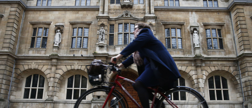 A woman rides a bike next to the Oriel College building with the statue of Cecil Rhodes on its facade in Oxford, southern England, December 30, 2015. REUTERS/Eddie Keogh/File Photo - RTSOWM6