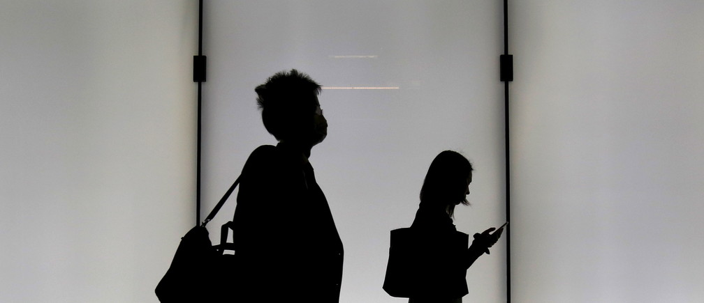 A man and a woman are silhouetted as they walk on an overpass at a business district in Tokyo, Japan, November 5, 2015. REUTERS/Yuya Shino - GF20000046606