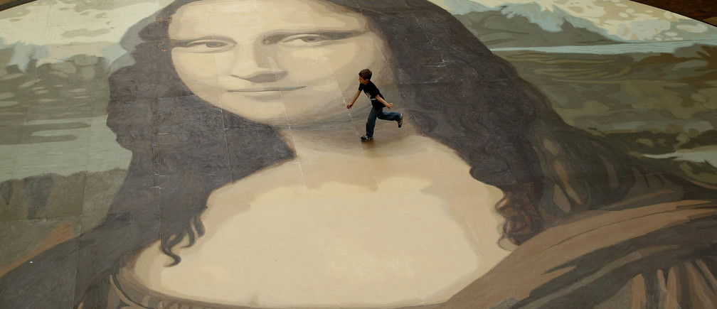 A boy runs across a giant copy of the Mona Lisa as it is unveiled in Wrexham, north Wales, October 28, 2009. The giant version of Leonardo da Vinci's masterpiece measuring 17.5 metres across and 50 times bigger than the original, is an attempt to produce the largest ever reproduction of the painting. REUTERS/Phil Noble (BRITAIN ENTERTAINMENT SOCIETY) - GM1E5AS1ENG01