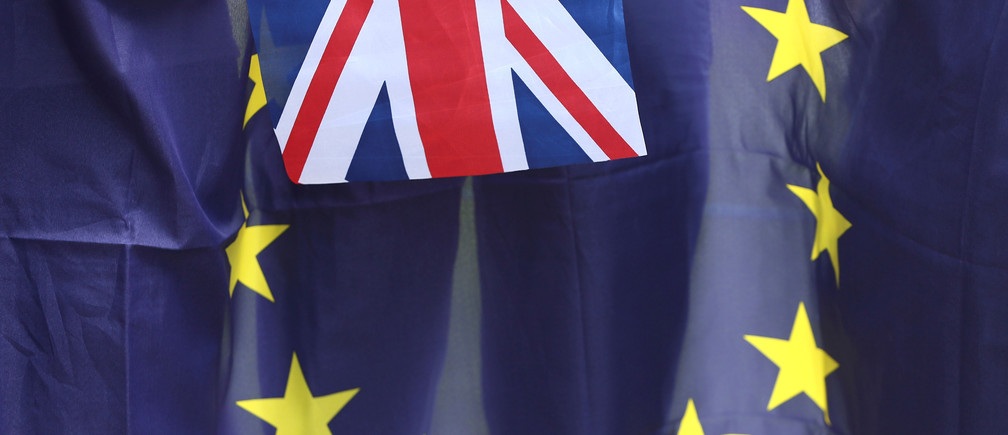 A British Union flag flies in front of an EU flag during a pro-EU referendum event at Parliament Square