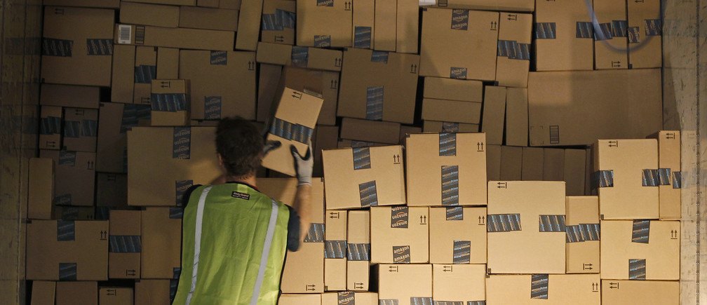 A worker stacks a shipping trailer with boxed items for delivery at Amazon's distribution center in Phoenix, Arizona November 22, 2013. The web-based retailer is preparing for Cyber Monday, traditionally the busiest day of the year for online purchases, which falls on December 2 in 2013. REUTERS/Ralph D. Freso   (UNITED STATES - Tags: BUSINESS EMPLOYMENT) - GM1E9BN0UTE01