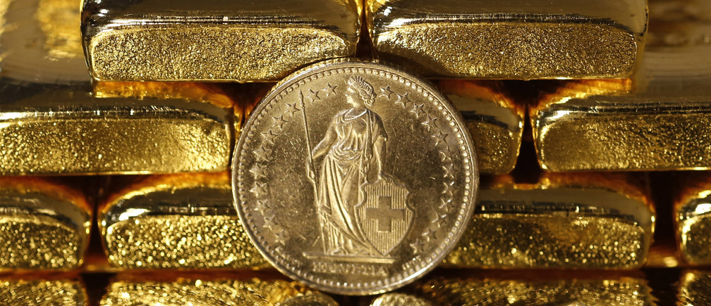 """Gold bars and a Swiss Franc coin are seen in this illustration picture taken at the Austrian Gold and Silver Separating Plant 'Oegussa' in Vienna November 7, 2014. A vote in favour of Switzerland boosting its gold reserves would be disastrous for the country, the chairman of the Swiss central bank said in a newspaper interview published on Thursday. The """"Save our Swiss gold"""" proposal, spearheaded by the right-wing Swiss People's Party (SVP), aims to ban the central bank from offloading its reserves and oblige it to hold at least 20 percent of its assets in gold. The referendum is scheduled for November 30. The SVP argues it would secure a stable Swiss franc. Picture taken November 7, 2014.      REUTERS/Leonhard Foeger (AUSTRIA) - LR1EABA163FI9"""