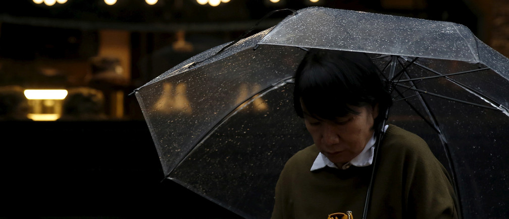 "A pedestrian holding an umbrella and her wallet walks past the word ""CASH"", part of a sign on a street at a shopping district in Tokyo, Japan, March 7, 2016.  REUTERS/Yuya Shino/File Photo - RTX2F99S"