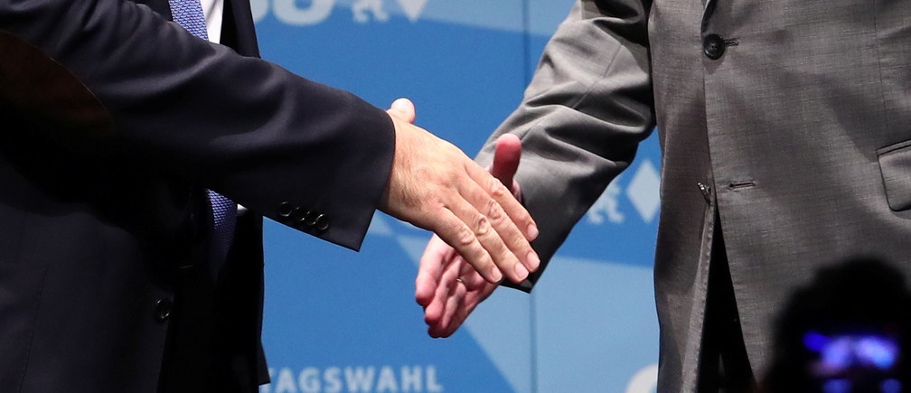 Leader of the Christian Social Union (CSU) Horst Seehofer and Bavarian State Prime Minister Markus Soeder shake hands on stage during a CSU election campaign rally in Ingolstadt, Germany, October 8, 2018. REUTERS/Michael Dalder - RC1629CE9ED0