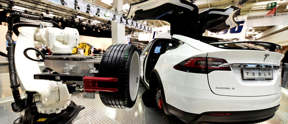 "A robotic arm changes the tyre of a Tesla car at the world's biggest industrial fair, ""Hannover Fair"", in Hanover, Germany April 24, 2017. REUTERS/Fabian Bimmer"