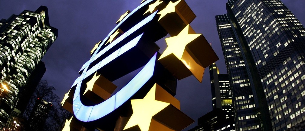 The illuminated euro sculpture is seen in front of the European Central Bank's (ECB) headquarter (R) in Frankfurt, February 1, 2005. Despite US Federal Reserve looks set to raise its key interest rates this week the ECB is expected to hold its rates until later this year. - RTXN7EA