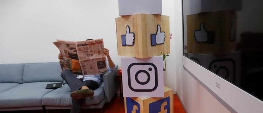 A man reads a newspaper at the reception area of Facebook's new office in Mumbai, India May 27, 2016.