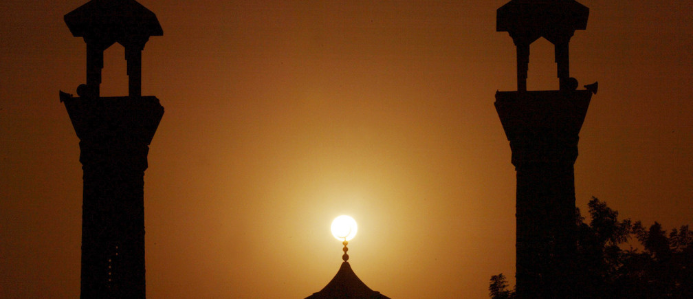 The sun sets behind a mosque during Ramadan in Dubai, UAE, October 16 2004. Ramadan, the ninth and holiest month of the Islamic lunar calendar, is a one month period of time during which devout Muslims refrain from all food, drink and sexual relations during daylight hours and focus on devotion alms and good deeds. REUTERS/Anwar Mirza. NO RIGHTS CLEARANCES OR PERMISSIONS ARE REQUIRED FOR THIS IMAGE.  AM/ABP - RP5DRHZMJZAB