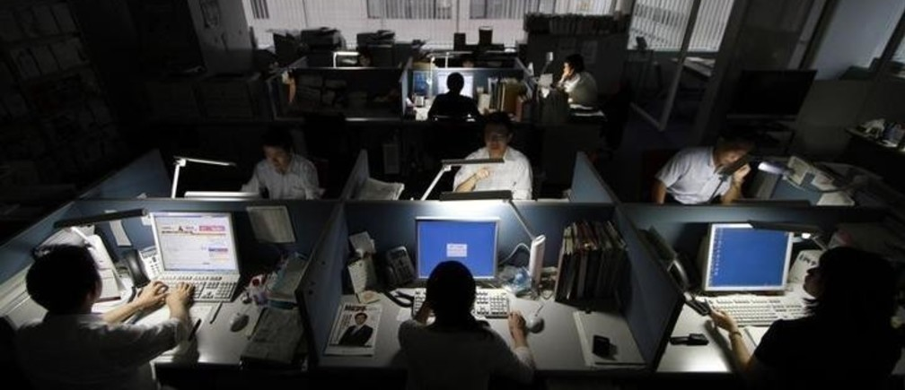 Employees of SMBC Nikko Securities Inc. work using only LED desk lights, during daytime at the company office in Tokyo June 30, 2011, a day before a target to cut electricity use by 15 percent in regions affected by Japan's March 11 earthquake and tsunami takes effect. The cuts are aimed at helping avoid power blackouts during the peak summer demand period amid efforts to restore generating capacity lost in the disaster.  REUTERS/Toru Hanai (JAPAN - Tags: DISASTER ENERGY BUSINESS)