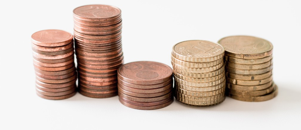stacked round gold-colored coins on white surface gdp economics money piles wealth uneven inequality equality growth projections finance commerce monetary fund funds pounds sterling dollar euro coppers coins cent penny pennies purse chancellor