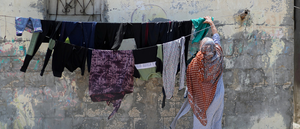 A Palestinian woman hangs laundry to dry outside her house at the Beach refugee camp in Gaza City June 18, 2020. Picture taken June 18, 2020. REUTERS/Mohammed Salem - RC27CH9J3R1S