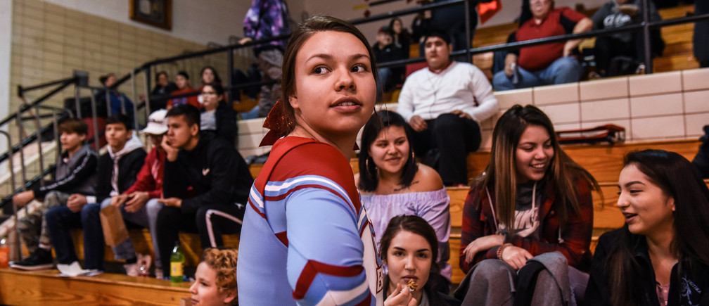 A cheerleader stops to talk with some spectators while attending a high school basketball game on the Cheyenne River Reservation in Eagle Butte, South Dakota, U.S. January 26, 2019. Picture taken January 26, 2019.  REUTERS/Stephanie Keith - RC1FB9A1D3B0
