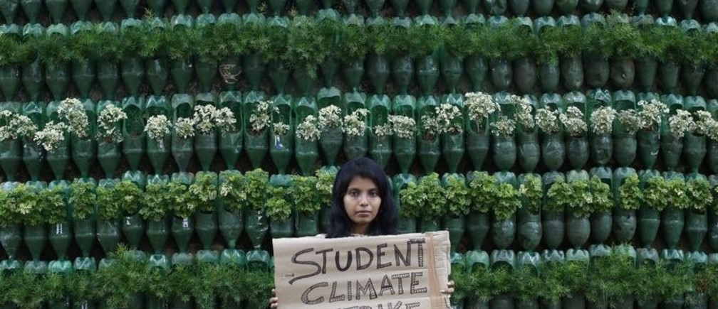 A participant holds up a placard as she takes part in a protest march demanding urgent measures to combat climate change, in Kolkata, India, June 7, 2019. REUTERS/Rupak De Chowdhuri - RC18DC7C3F20